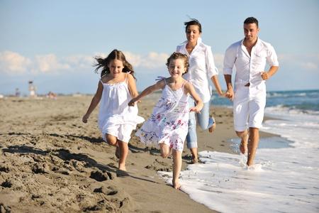 Foto de happy young family in white clothing have fun at vacations on beautiful beach  - Imagen libre de derechos