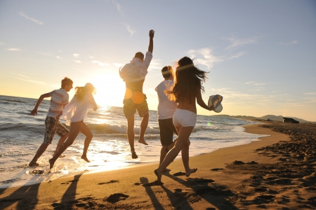 Foto de happy young people group have fun white running and jumping on beacz at sunset time - Imagen libre de derechos