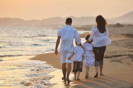 Foto de happy young family have fun on beach run and jump  at sunset - Imagen libre de derechos