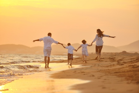 Photo for happy young family have fun on beach run and jump  at sunset - Royalty Free Image