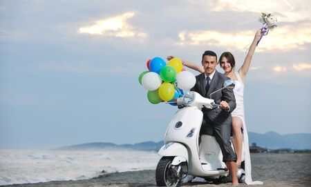 Photo pour wedding scene of bride and groom just married couple on the beach ride white scooter and have fun - image libre de droit