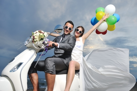 Foto de wedding sce of bride and groom just married couple on the beach ride white scooter and have fun - Imagen libre de derechos