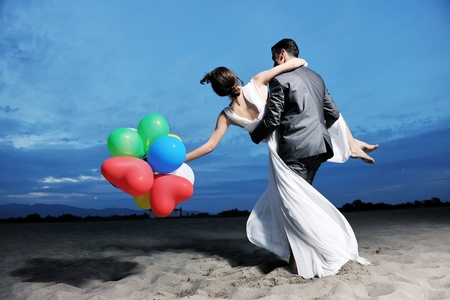Photo for happy just married young couple celebrating and have fun at beautiful beach sunset - Royalty Free Image