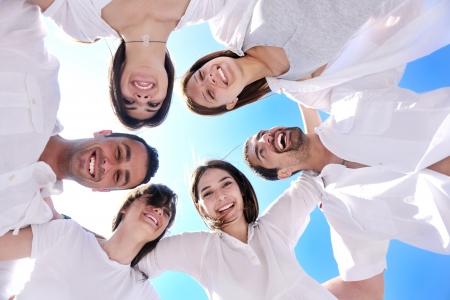 Foto de Group of happy young people in circle at beach  have fun and smile - Imagen libre de derechos