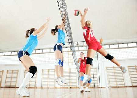 Foto de volleyball game sport with group of young beautiful  girls indoor in sport arena - Imagen libre de derechos