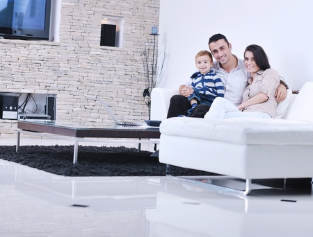 Foto de happy young family have fun and relaxing at new home with modern lcd tv in background - Imagen libre de derechos