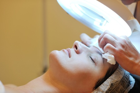 Young beautiful woman receiving cosmetic facial mask in spa beauty salon and relaxの写真素材