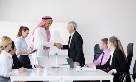 Business meeting - Handsome young Arabic  man presenting his ideas to colleagues and listening for ideas for success investments at bright modern office roomの写真素材