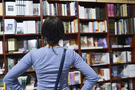 Pretty female student standing at bookshelf in university library store shop  searching for a book