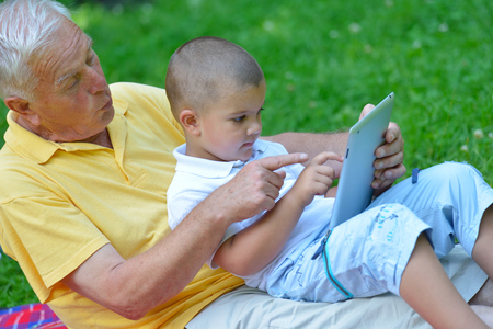 grandfather and child in park using tablet computer