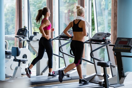 Foto de Beautiful group of young women friends  exercising on a treadmill at the bright modern gym - Imagen libre de derechos