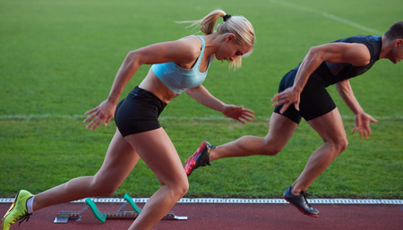 Foto de athlete woman group  running on athletics race track on soccer stadium and representing competition and leadership concept in sport - Imagen libre de derechos