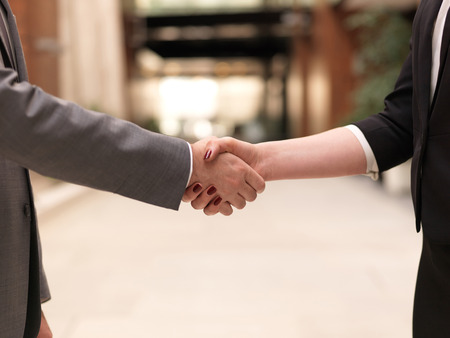 business partners concept with businessman and businesswoman handshake at modern office indoorsの写真素材