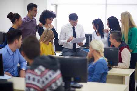 Foto de group of students with teacher in computer lab classrom learrning lessons,  get help and support - Imagen libre de derechos