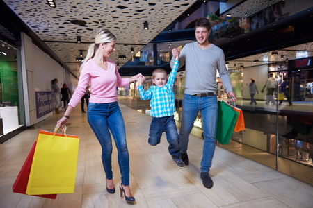happy  young family with shopping bags in mallの写真素材
