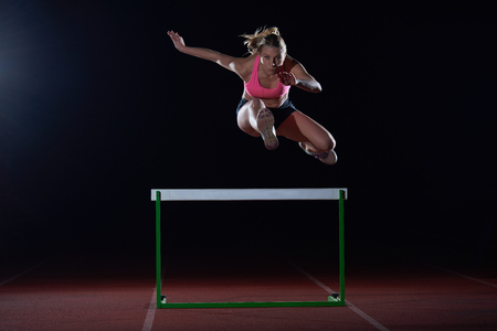 Determined young woman athlete jumping over a hurdles