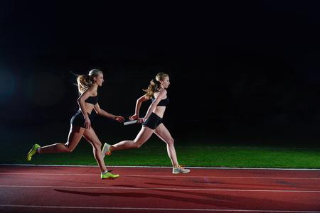 Photo pour woman athletic runners passing baton in relay race - image libre de droit