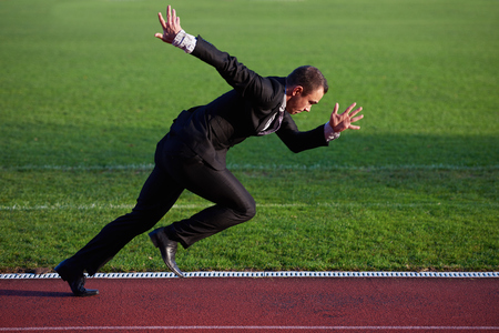 Photo pour business man in start position ready to run and sprint on athletics racing track - image libre de droit