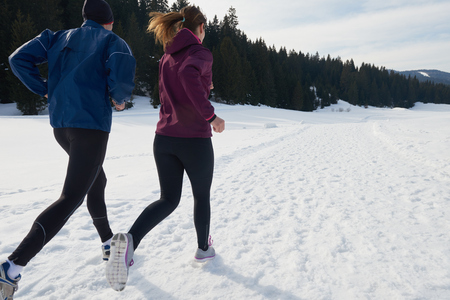 healthy young couple jogging outside on snow in forest. athlete running on  beautiful sunny winter dayの写真素材