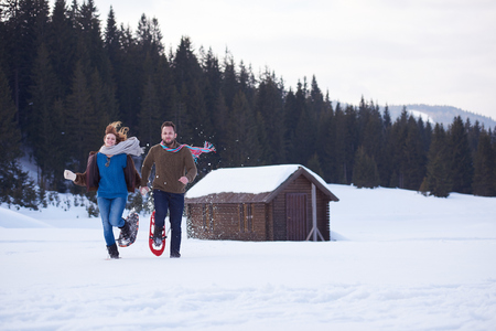 happy young  couple having fun and walking in snow shoes. Romantic winter relaxation sceneの写真素材