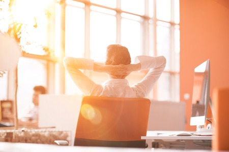 Photo for Happy young business woman relaxing and geting insiration while working on desktop computer at modern bright  starup office interior. Morning sunrise or sunset with sun flare in background. - Royalty Free Image