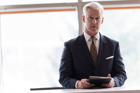 Foto per handsome senior business man with grey hair working on tablet computer at modern bright office interior - Immagine Royalty Free