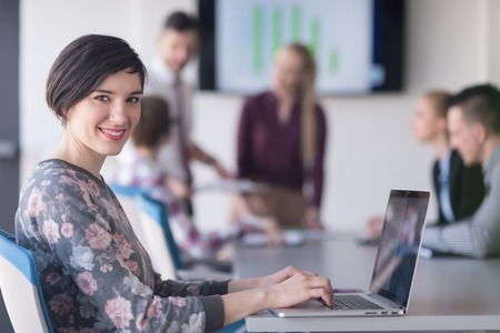 Photo for young  business woman at modern startup office interior working on laptop computer, blured team in meeting, people group in background - Royalty Free Image