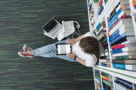 female student study in school library, using tablet and searching for information's on internet. Listening music and lessons on white headphones