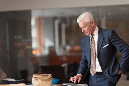 Foto de senior business man reading reports on tablet computer at modern office interior - Imagen libre de derechos