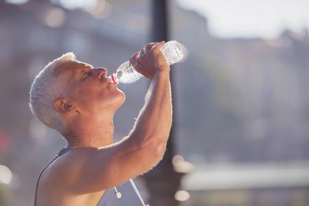 Photo pour handsome senior jogging man drinking fresh water from bottle after mornig run - image libre de droit