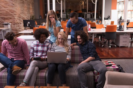 Photo for Multiethnic startup business team on meeting in modern bright office interior brainstorming, working on laptop and tablet computer - Royalty Free Image