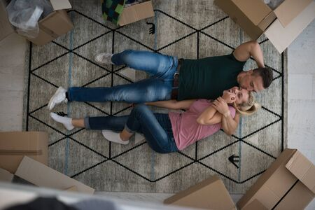 Top view of attractive young couple moving, holding hands, looking at camera and smiling while lying among cardboard boxes