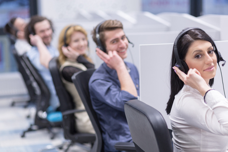 Foto de group of young business people with headset working and giving support to customers in a call center office - Imagen libre de derechos