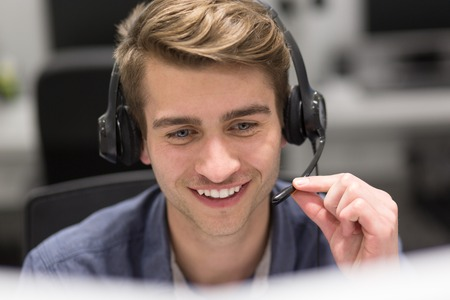 Foto de young smiling male call centre operator doing his job with a headset - Imagen libre de derechos