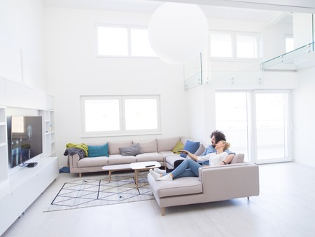 Photo pour Young couple on the sofa watching television together in their luxury home - image libre de droit