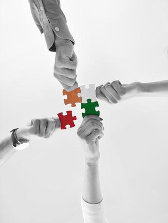 Foto de Group of business people assembling jigsaw puzzle and represent team support and help concept - Imagen libre de derechos