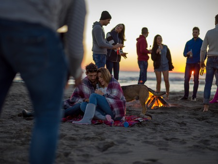 Young Couple Sitting with friends Around Campfire on The Beach At sunset drinking beer