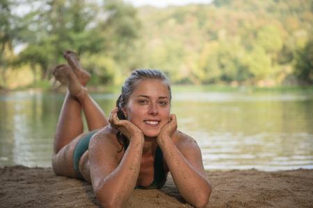 Photo pour a beautiful sexy girl in a green bikini relaxing and enjoying in nature on the riverbank - image libre de droit