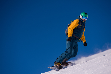 Young freestyle snowboarder running down the slope and ride free style at sunny winter day on Alpine mountains.