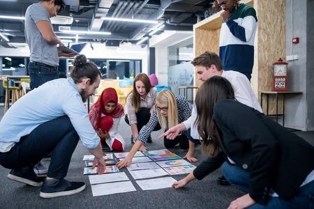 Foto de young black muslim businesswoman having meeting with her multiethnic startup business team in modern office interior,presenting new ideas on the floor - Imagen libre de derechos