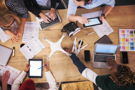 Foto de multiethnic startup business team discussing new business plan,working on laptop and tablet computer while learning about drone technology for future business ventures top view - Imagen libre de derechos