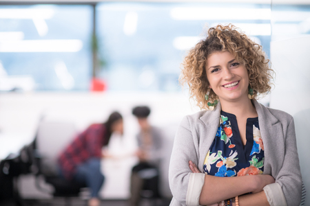 Foto de Portrait of successful female software developer with a curly hairstyle at modern startup office - Imagen libre de derechos