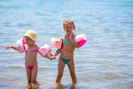 Photo pour Two happy little girls with swimming armbands playing in shallow water of the sea during Summer vacation  Healthy childhood lifestyle concept - image libre de droit