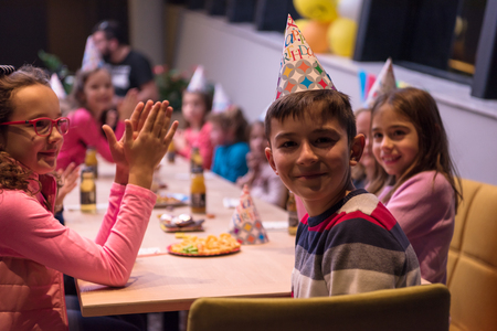 Photo for The young boy joyfully celebrating his birthday with a group of his friends - Royalty Free Image