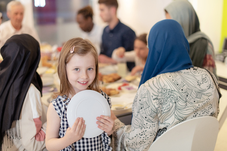 Photo pour cute little girl enjoying iftar dinner together with modern multiethnic muslim family in the background  during a ramadan feast at home - image libre de droit