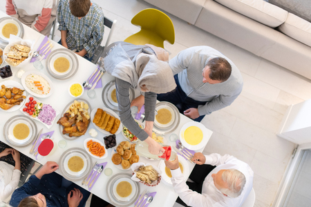 Photo pour top view of modern multiethnic muslim family enjoying eating iftar dinner together during a ramadan feast at home - image libre de droit