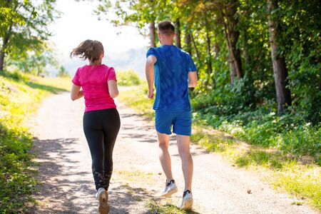 Photo pour young happy couple enjoying in a healthy lifestyle while jogging on a country road through the beautiful sunny forest, exercise and fitness concept - image libre de droit