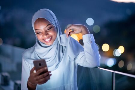 Photo pour Young modern Muslim woman wearing scarf veil on urban city  street at night texting on smartphone with bokeh city light in background - image libre de droit