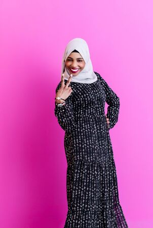Photo pour portrait of young modern muslim afro beauty wearing traditional islamic clothes on plastic pink background - image libre de droit