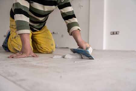 Photo pour Grouting ceramic tiles. Tilers filling the space between ceramic wood effect tiles using a rubber trowel on the floor in new modern apartment - image libre de droit